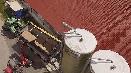 Luftaufnahme von Stall, Silos und Wärmetauscher. Außerdem wird Weizen verladen.