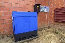 Rechteckiger blauer Behälter für Betriebsmittel an Stallwand