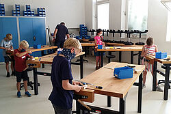 Kinder tüfteln an Werkbänken