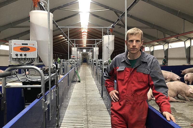 Landwirt steht in langem Korridor mit Buchten links und rechts
