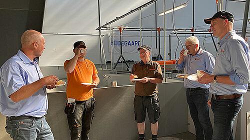 Fünf Männer essen und trinken im Stall und unterhalten sich.