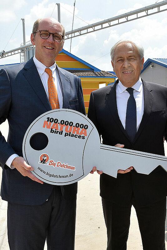 Zwei Männer halten einen großen Schlüssel in Händen