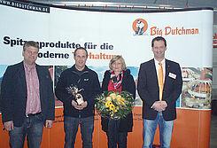 Hähnchenmast: Zur Einweihung von Geflügelstall und Stalleinrichtungen überreichen Big Dutchman-Mitarbeiter Geschenke